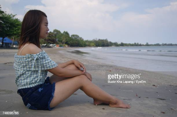 Full Length Side View Of Young Woman Sitting At Beach Against Sky