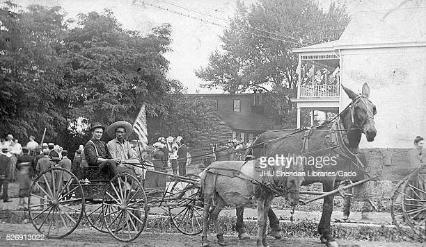 Full length sitting portraits of young African American and young white males sitting in wagon driven by a pony and a horse riding in parade white...