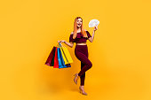 Full length size body portrait of red straight-haired beautiful young girl, wearing suit, pants, top blouse, holding shop bags and fan of dollars cash. Isolated over bright vivid yellow background