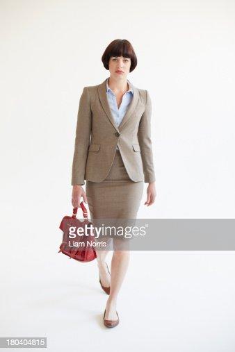 Full length studio shot of businesswoman with red handbag
