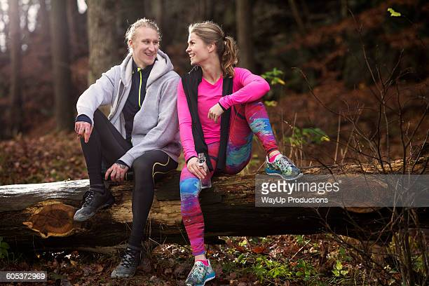 Full length view of couple wearing sports clothing sitting on fallen tree, smiling