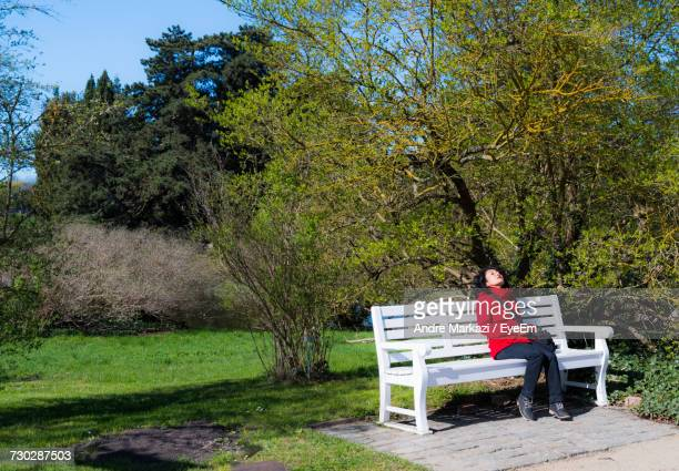 Full Length Woman Relaxing On Bench At Park