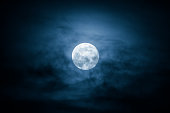 Full Moon and clouds on the night sky.