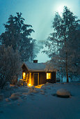 Traditional finnish sauna building on winter landscape with full moon.