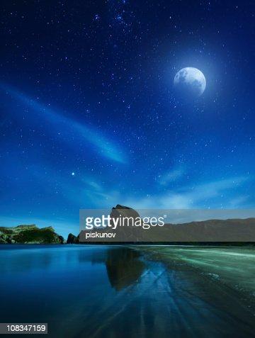 Full moon and rocky coast : Stock Photo