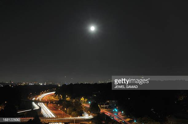 A full moon appears over a highway as late traffic make its way in Newton Massachusetts on September 30 2012 AFP PHOTO/Jewel Samad