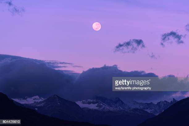 Full moon at pink sunrise over mountain peak