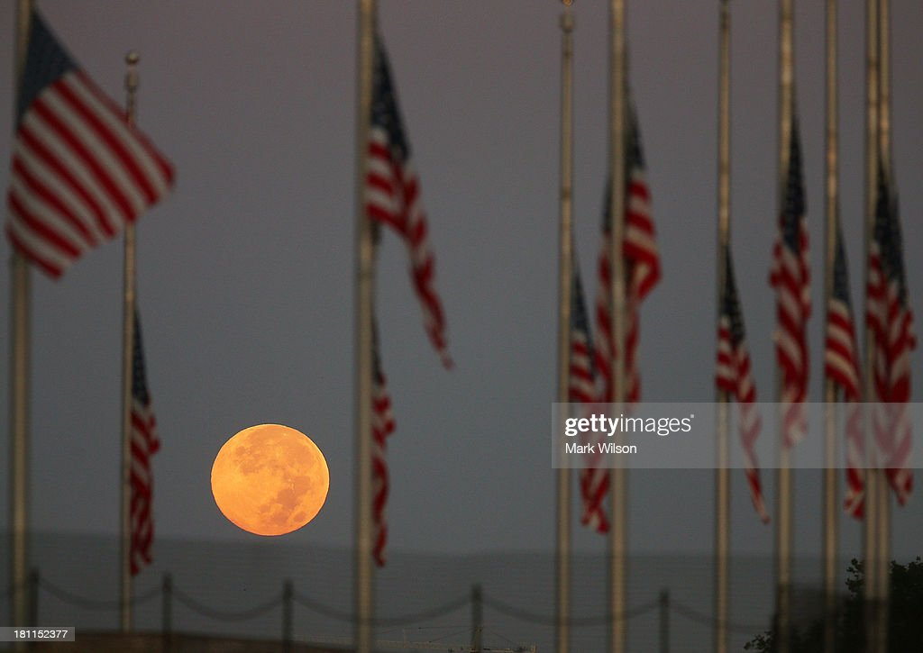 A full moon glows behind flags at the Washington Monument that have been lowered to half staff to honor the victims of Monday's shooting at the Washington Navy Yard, September 19, 2013 in Washington, DC. Aaron Alexis on September 16, 2013 entered a building at the Washington Navy Yard and shot and killed 12 people before being shot and killed by police.