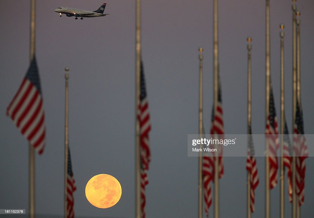 A full moon glows behind flags at the Washington Monument that have been lowered to half staff to honor the 12 shooting victims this week at the Washington Navy Yard on September 19, 2013 in Washington, DC. Senate Democratic leaders today will hold a news conference at the Capitol while the House and Senate GOP will discuss the continuing resolution to defund Obamacare.