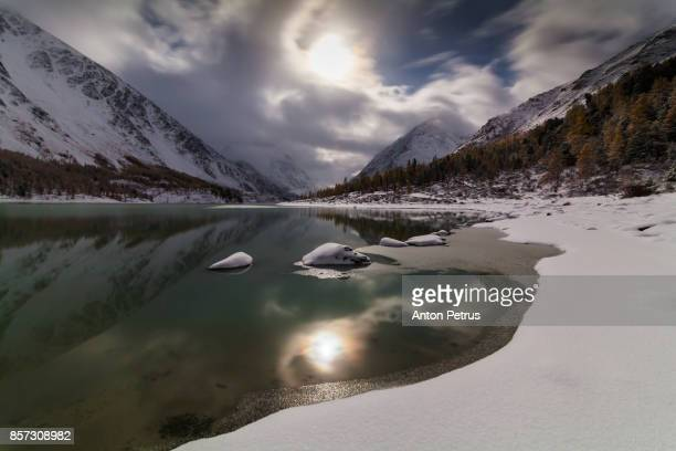 Full moon in the mountains on the shore of a snow-covered lake