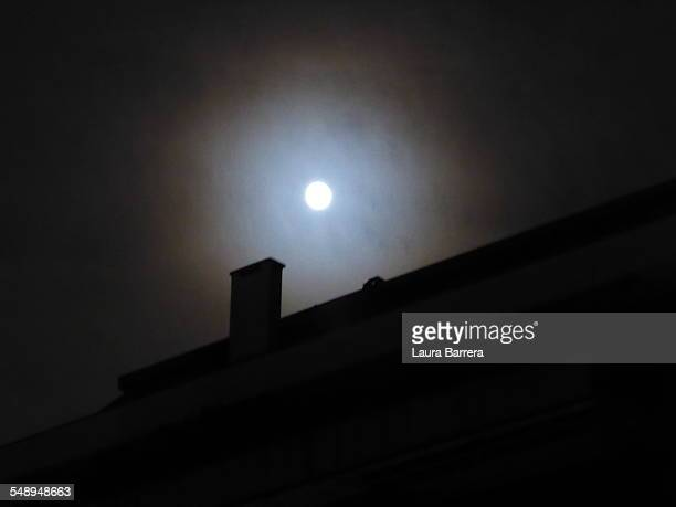 Full moon over a roof
