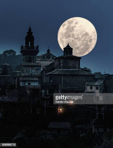 full moon over medieval village at night
