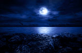 Full moon over the ocean with clouds and rocks