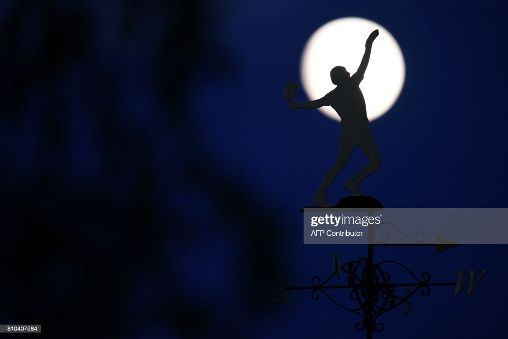TOPSHOT - A full moon rises beyond a tennis-themed weather vane at The All England Lawn Tennis Club in Wimbledon, southwest London, on July 7, 2017 on the fifth day of the 2017 Wimbledon Championships. / AFP PHOTO / Oli SCARFF / RESTRICTED