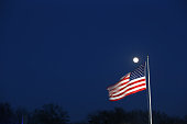 A full moon rises over a US flag on March 22 2016 in Groton CT Communities across New England are struggling with the unprecidented heroin and opioid...