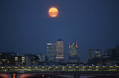 A full moon rises over Canary Wharf on September 9 2014 in London England A supermoon or harvest moon involves a full moon coinciding with it's...
