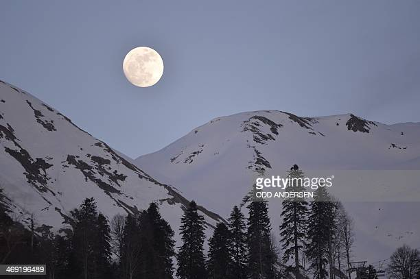 A full moon rises over the mountains during the Men's Biathlon 20 km Individual at the Laura CrossCountry Ski and Biathlon Center during the Sochi...