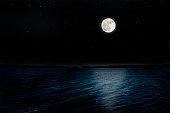 Full moon rising over the peninsula with lots of shining stars from shining night sea.