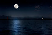 Full moon rising over the sea and the lighthouse with copy space.