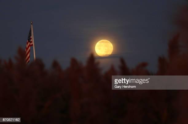 A full moon sets at sunrise over the Richard W De Korte Park on November 4 2017 in Lyndhurst New Jersey