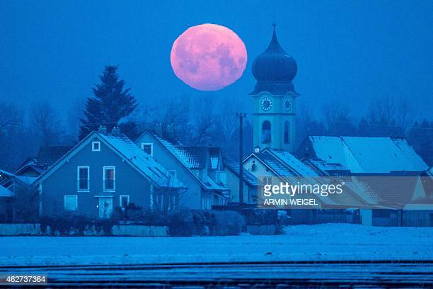 Full moon sets behind the parish church of Schoenach near Regensburg southern Germany on February 4 2015 AFP PHOTO / DPA / ARMIN WEIGEL GERMANY OUT