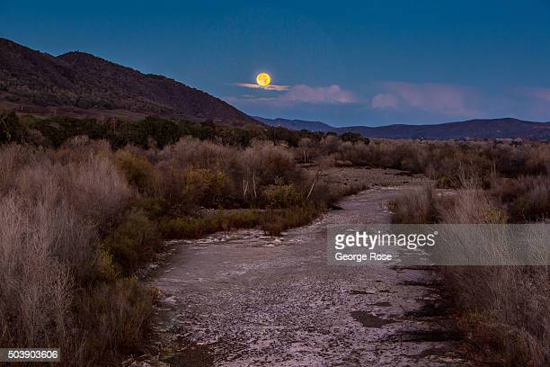 A full moon sets over a dry Santa Ynez River on December 25 in Solvang California Because of its close proximity to Southern California and Los...