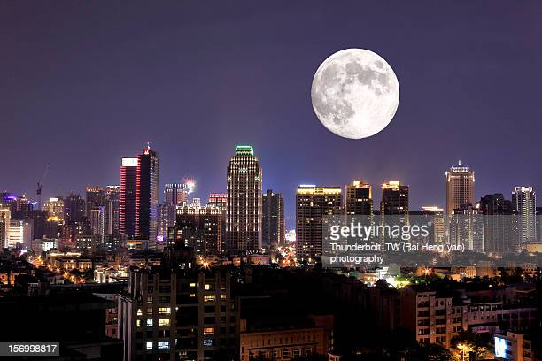 full moon upon lights of city