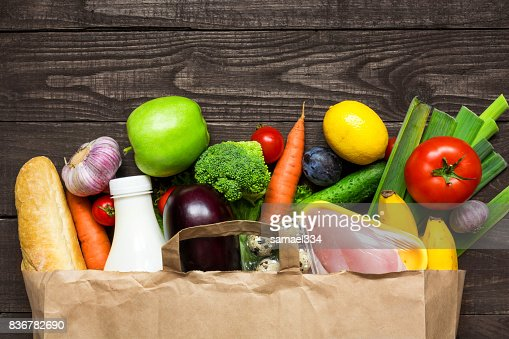Full paper bag of different health food on rustic wooden background : Foto stock