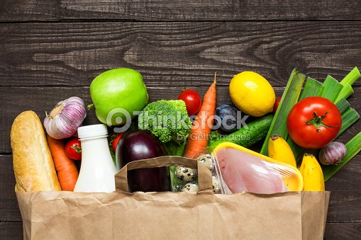 Full paper bag of different health food on rustic wooden background : Stock Photo
