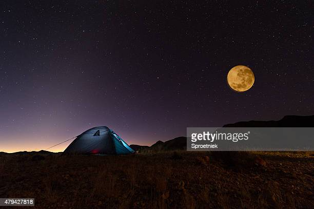 Full red moon and stars over lit tent in desert