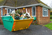 A full rubbish skip beside a house that has been filled up by the householder.