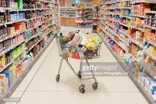 Full shopping cart in supermarket aisle