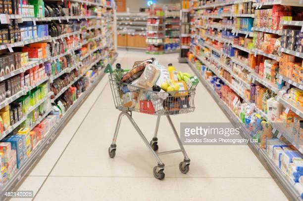 Full shopping cart in supermarket aisle