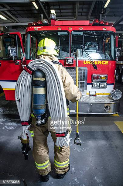 Full shot of fireman wearing full protection equipment and truck