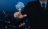 Businessman pressing button 24 hours service icon over blur colorful night light city tower, Full time service concept