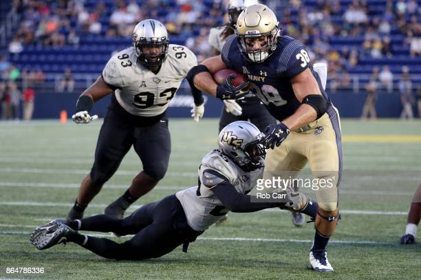 Fullback Anthony Gargiulo of the Navy Midshipmen rushes for a second half touchdown while being tackled by defensive back Josh Kelly of the UCF...