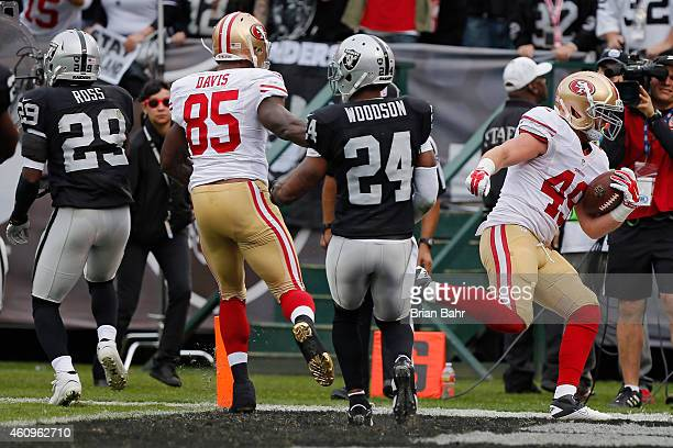 Fullback Bruce Miller of the San Francisco 49ers carries a short pass for an eightyard gain into the end zone against safeties Brandian Ross and...