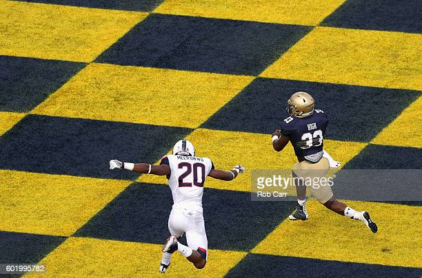Fullback Chris High of the Navy Midshipmen scores a first quarter touchdown in front of safety Obi Melifonwu of the Connecticut Huskies at NavyMarine...