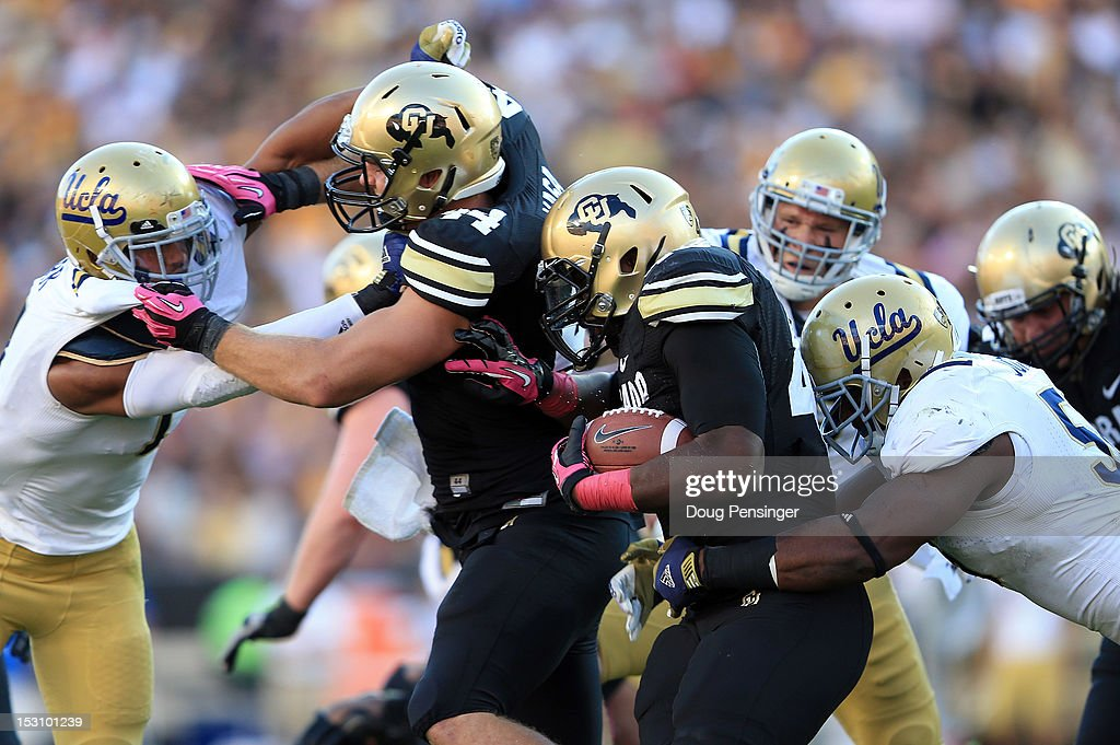Fullback Christian Powell #46 of the Colorado Buffaloes is tackled by defensive end Datone Jones #56 of the UCLA Bruins as tight end Nick Kasa #44 of the Colorado Buffaloes blocks linebacker Anthony Barr #11 of the UCLA Bruins at Folsom Field on September 29, 2012 in Boulder, Colorado.