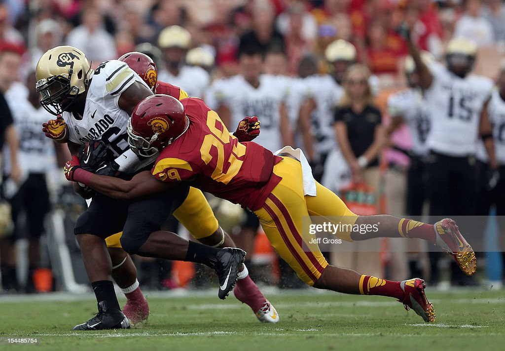 Fullback Christian Powell #46 of the Colorado Buffaloes is tackled by safety Jawanza Starling #29 of the USC Trojans in the first quarter at Los Angeles Memorial Coliseum on October 20, 2012 in Los Angeles, California. USC defeated Colorado 50-6.