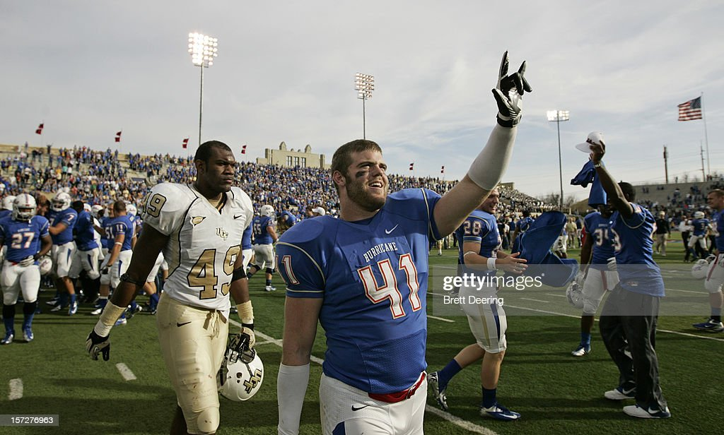 Fullback Cody Wilson #41 of the Tulsa Golden Hurricane celebrates as defensive lineman Cam Henderson #49 of the Central Florida Knights walks off the field after the C-USA championship game on December 1, 2012 at H.A. Chapman Stadium in Tulsa, Oklahoma. Tulsa defeated Central Florida 33-27 in overtime.
