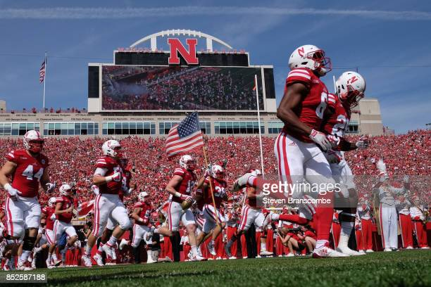 Fullback Harrison Jordan of the Nebraska Cornhuskers carries the flag as the team enter the field against the Rutgers Scarlet Knights at Memorial...