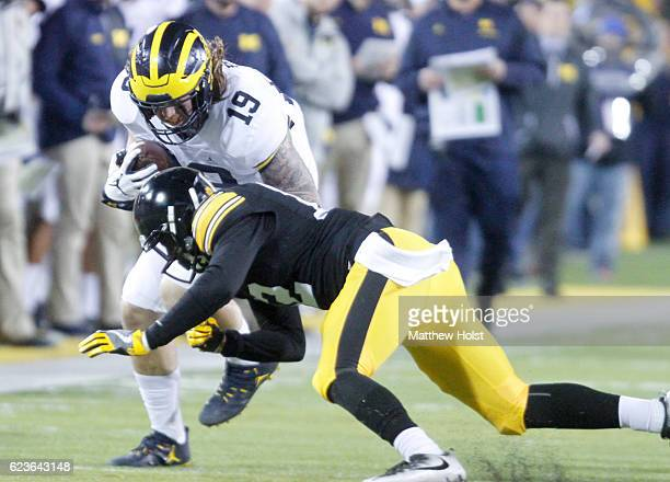 Fullback Henry Poggi of the Michigan Wolverines rushes up field during the first quarter against defensive back Anthony Gair of the Iowa Hawkeyes on...