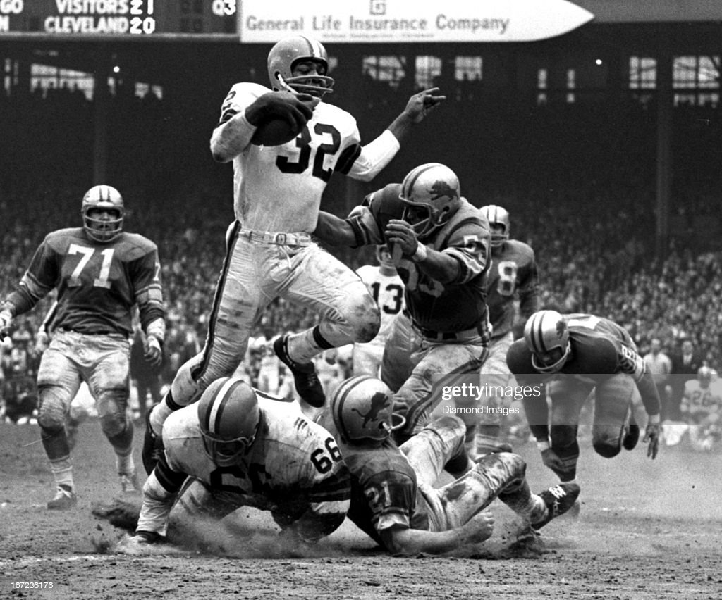 Fullback Jim Brown #32 of the Cleveland Browns runs through the defense during a game on November 15, 1964 against the Detroit Lions at Cleveland Municipal Stadium in Cleveland, Ohio. Cleveland won 37-21.