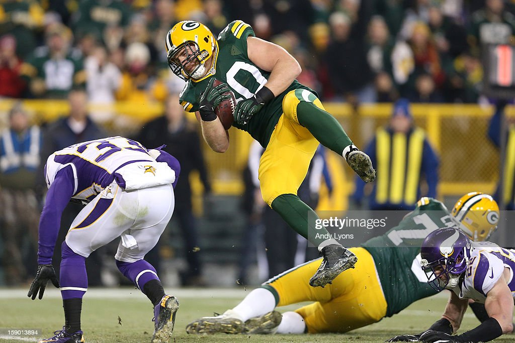 Fullback John Kuhn #30 of the Green Bay Packers flies over safety Jamarca Sanford #33 of the Minnesota Vikings to score on a nine-yard touchdown catch and run in the third quarter against the Minnesota Vikings during the NFC Wild Card Playoff game at Lambeau Field on January 5, 2013 in Green Bay, Wisconsin.