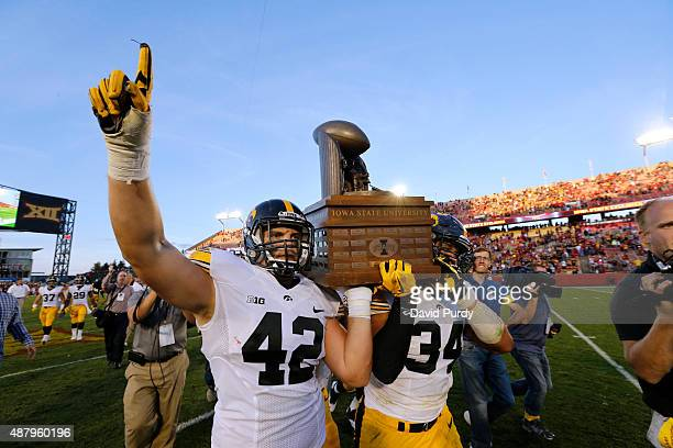 Fullback Macon Plewa and defensive end Nate Meier of the Iowa Hawkeyes carry the CyHawk Trophy to fans after defeating the Iowa State Cyclones 3117...
