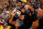 Fullback Mark Cosgrove of the Arizona State Sun Devils celebrates with the Territorial Cup after defeating the Arizona Wildcats 5237 in the college...