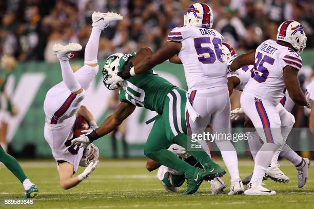 Fullback Patrick DiMarco of the Buffalo Bills is upended by outside linebacker Freddie Bishop of the New York Jets during the second half of the game...