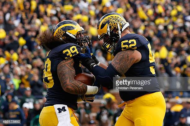 Fullback Sione Houma of the Michigan Wolverines celebrates with Mason Cole after Houma scored a two yard rushing touchdown against the Michigan State...