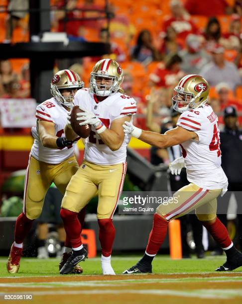 Fullback Tyler McCloskey of the San Francisco 49ers celebrates with teammates in the end zone after scoring a touchdown during the preseason game...